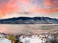 munți albi și maro lângă corpul de apă în timpul zilei