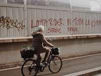 Mann in der braunen Jacke, die tagsüber auf schwarzem Fahrrad reitet