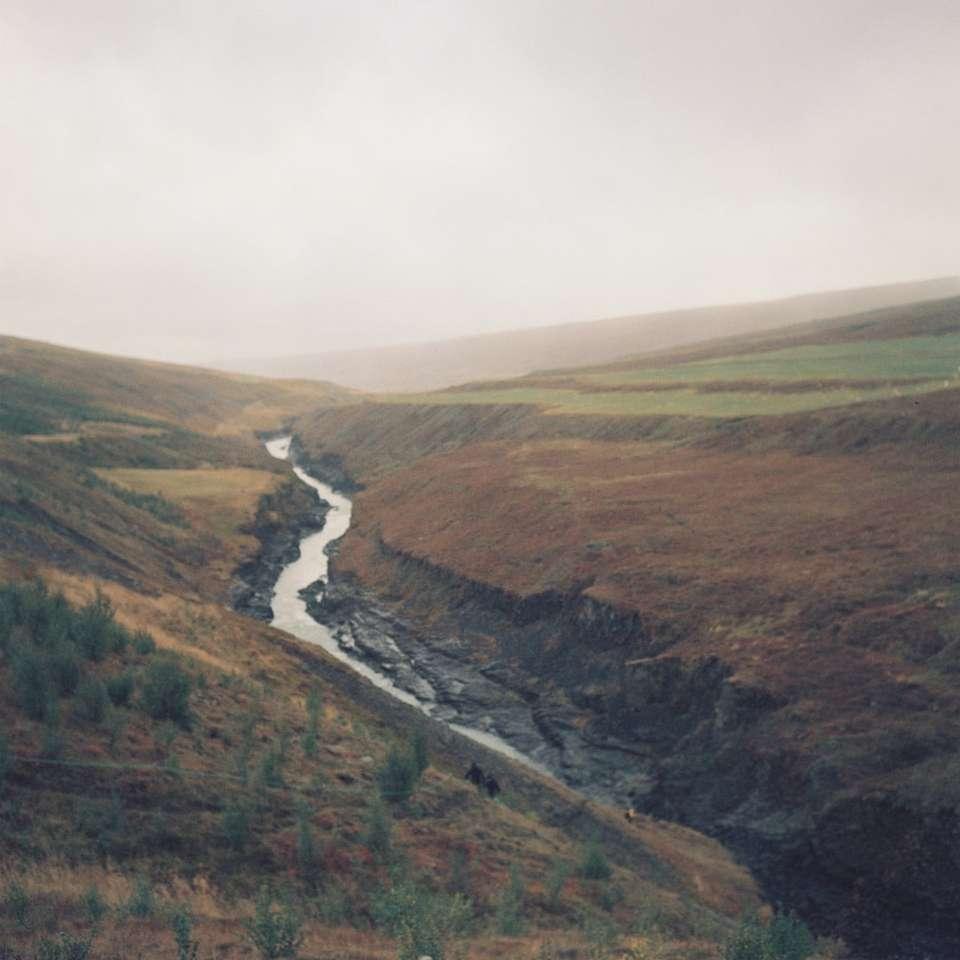 Fluss inmitten grüner und brauner Berge - Aufgenommen im Mittelformat abgelaufener Film mit Rolleiflex. Ein Tal und ein kleiner Fluss, die in Island durchfließen. Island (19×19)
