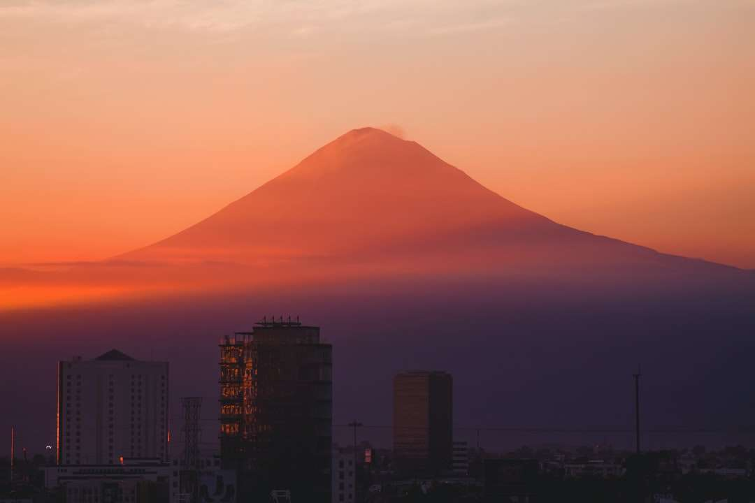 silhouette of mountain under cloudy sky during daytime - Beautiful red sunset behind the Popocatepetl, a mexican famous volcano located near the city of Puebla. The buildings make a perfect blend between nature and urban style. Puebla, Pue., México (4×3)