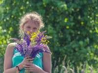 dziewczyna w niebieskiej sukience bez rękawów, trzymając fioletowy kwiat