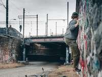 Mann in grauer Jacke und grauer Hose mit schwarzem Skateboard