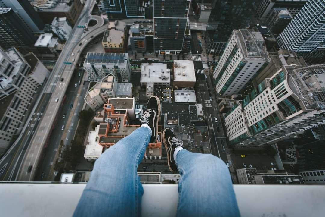 pessoa em jeans azul e tênis preto - pessoa em jeans azul e tênis preto, sentada no prédio de concreto branco durante o dia. Topo do mundo. São Francisco, CA, Estados Unidos (4×3)
