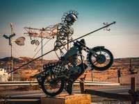 schwarzes und graues Motorrad geparkt auf braunem Holzpfosten