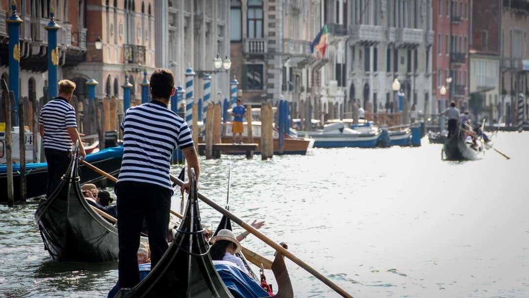muž v černé a bílé pruhované tričko na koni na lodi - muž v černé a bílé pruhované tričko, jízda na lodi na vodě během dne. . Benátky, Venedig, Itálie (14×8)