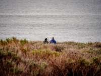 Mann und Frau sitzen auf Grasfläche in der Nähe von Gewässern