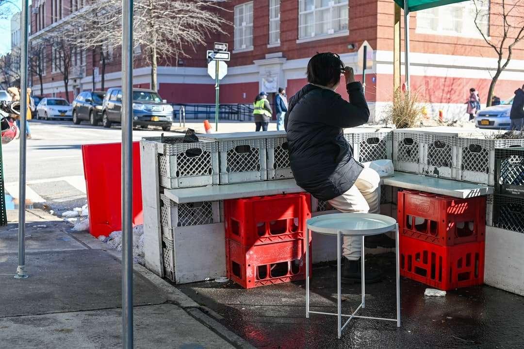 muž v černé bundě sedí na červené plastové sedadlo - Manhattan Ave & Conselyea St. Manhattan Ave & Conselyea Street, Brooklyn, NY, USA (13×9)