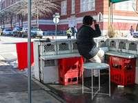 muž v černé bundě sedí na červené plastové sedadlo