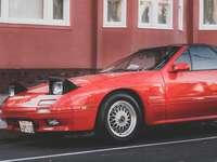 Porsche 911 rossa parcheggiata accanto all'edificio rosso