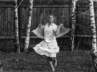chica en vestido blanco de pie en el campo de hierba