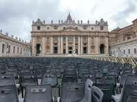 graue Stühle nahe braunem Betongebäude während des Tages