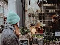 žena v modré pletené čepici a šedé bundě stojící vpředu