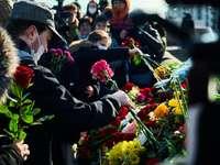 άντρας με μαύρο κοστούμι κρατώντας μπουκέτο λουλούδια
