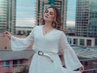 donna in abito bianco manica lunga in piedi vicino a ringhiere