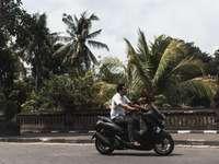 Mann im weißen Hemd reitet schwarzes Motorrad auf Straße