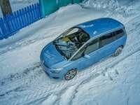 blaues 5-türiges Fließheck auf schneebedeckter Straße während des Tages