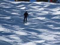 Person in schwarzer Jacke, die auf schneebedecktem Boden geht