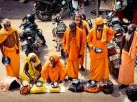 хора в оранжев халат, стоящи на мотоциклет през деня