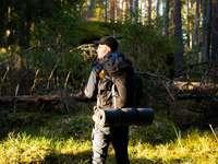 Mann in schwarzer Jacke und schwarzer Hose mit schwarzem Rucksack
