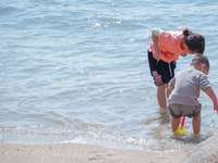 man in red shirt carrying child in white shirt on beach