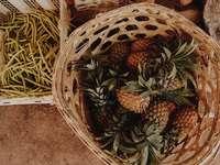 плодове от кафяв и зелен ананас върху кафява тъкана кошница