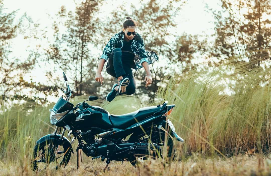 man in black t-shirt and black shorts riding - man in black t-shirt and black shorts riding on blue and black motorcycle during daytime (15×10)