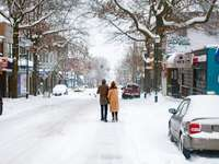 Mujer de abrigo marrón caminando por la carretera cubierta de nieve
