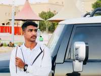 Hombre con camisa de vestir blanca de pie junto al coche plateado