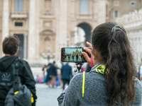 žena v šedá mikina drží černý smartphone