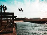 homem pulando de um penhasco para um lago