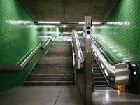 escada de concreto cinza com corrimão de metal verde