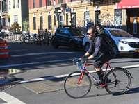 man i svart jacka som rider på röd cykel på vägen