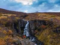 watervallen op bruine rotsachtige berg onder witte bewolkte hemel