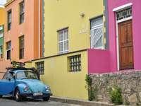 Coche azul aparcado junto al edificio de hormigón amarillo