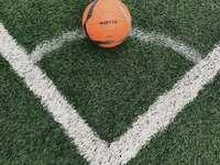 оранжева футболна топка на поле със зелена трева