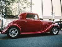 червена ретро кола на сив асфалтов път през деня