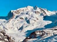 заснежена планина под синьо небе през деня