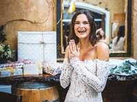 Frau im weißen blumigen schulterfreien Kleid lächelnd