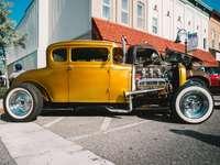 gelbes altes Auto, das nahe weißem Gebäude geparkt wird