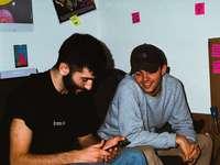 muž v šedém tričku s výstřihem do krku sedí vedle muže