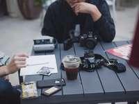 άντρας με μαύρο σακάκι που κάθεται δίπλα στο τραπέζι