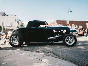Coche convertible negro sobre la carretera de asfalto gris durante el día