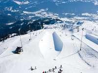ludzie jadący wyciągiem narciarskim na zaśnieżonej górze