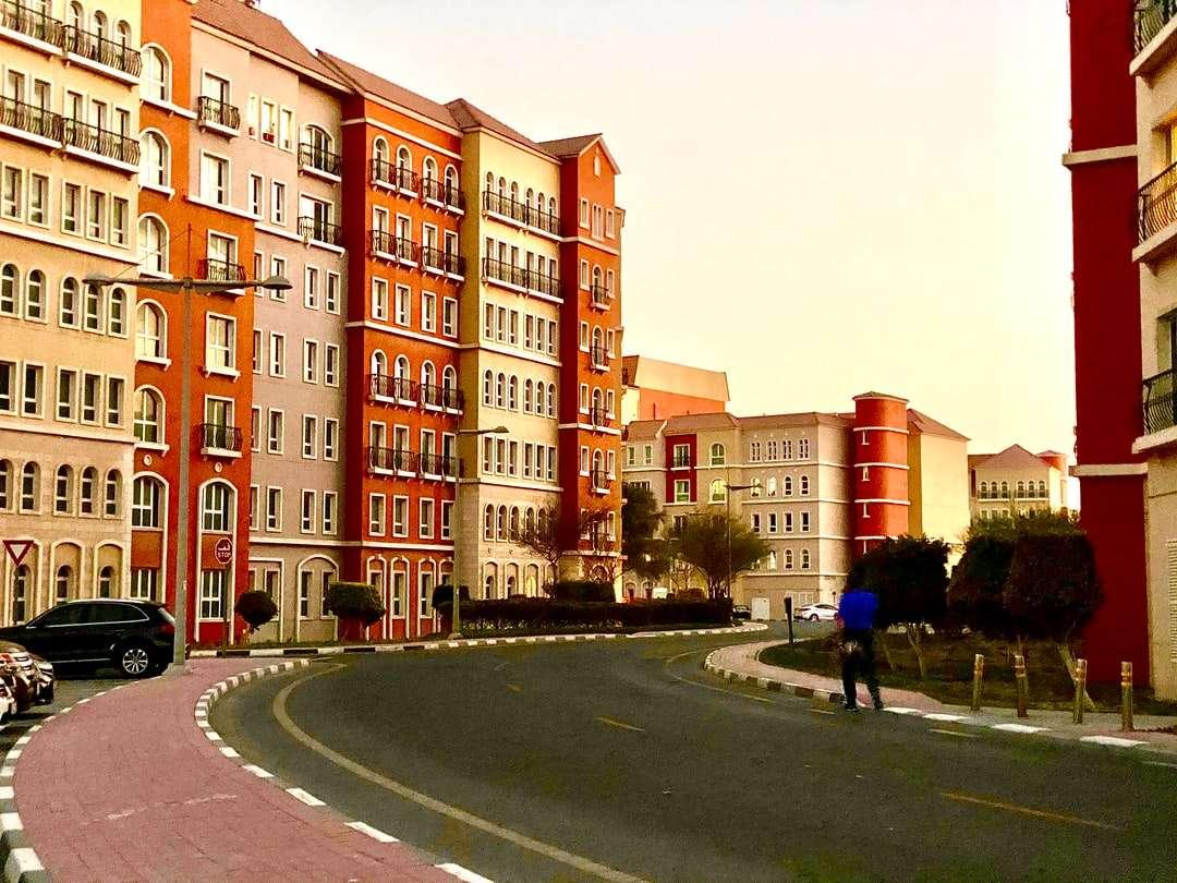 gente caminando en la calle cerca del edificio de hormigón marrón