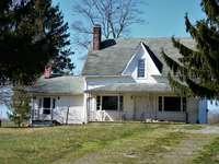 Бяла и кафява дървена къща близо до зелени дървета през деня