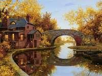 Casa de râu cu un pod în toamnă