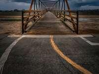 Podul brun din lemn peste mare sub nori albi