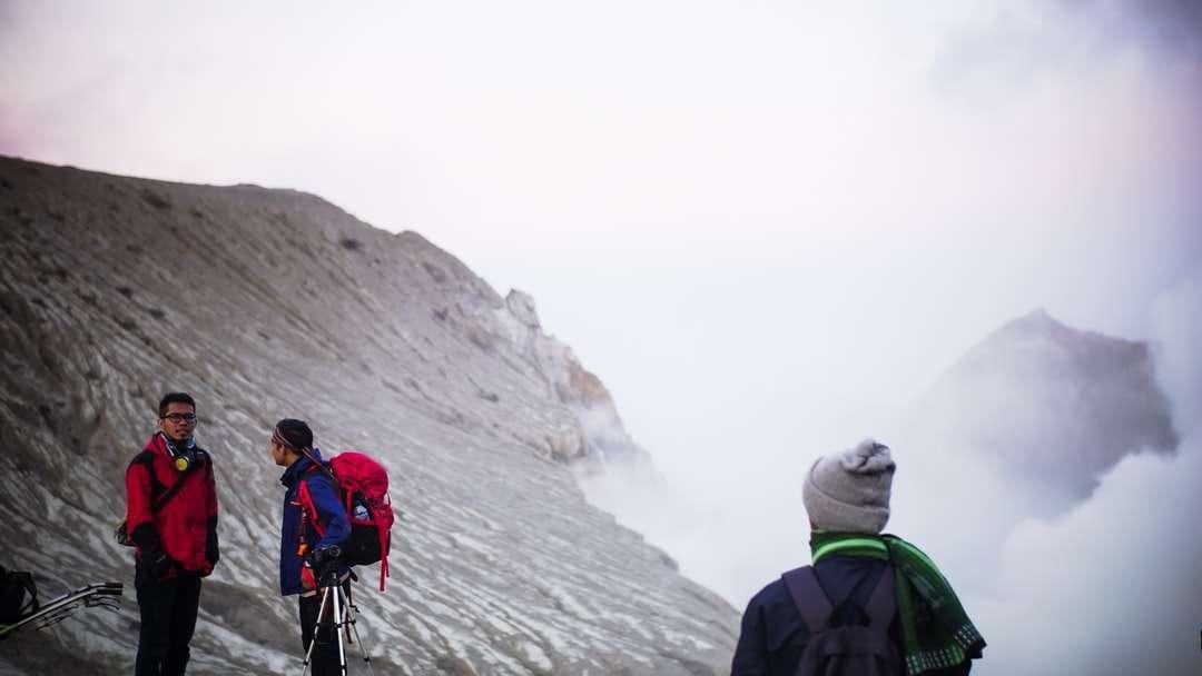 2 човек, облечен в раници, стоящи на скалиста планина