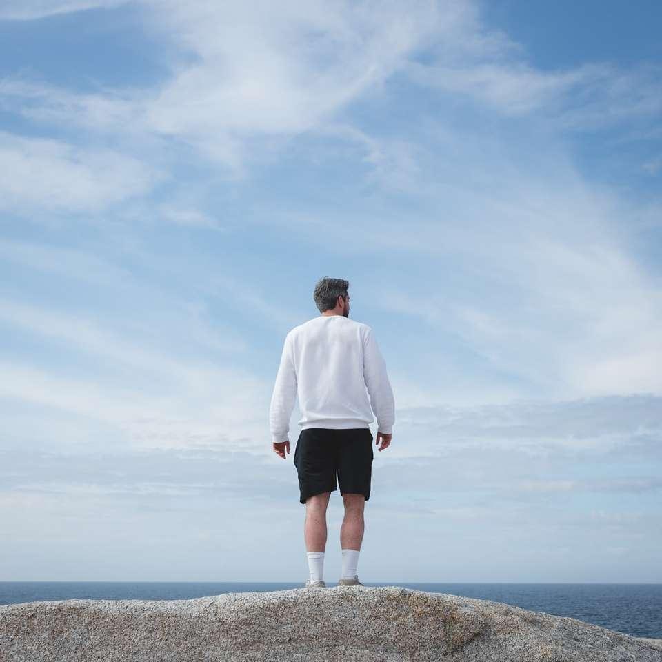 Man i vit långärmad tröja och svarta shorts online pussel