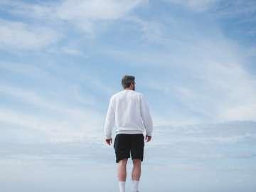 Man i vit långärmad tröja och svarta shorts